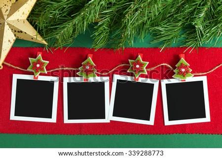 Polaroid photo frames hanging on rope over Christmas background - stock photo
