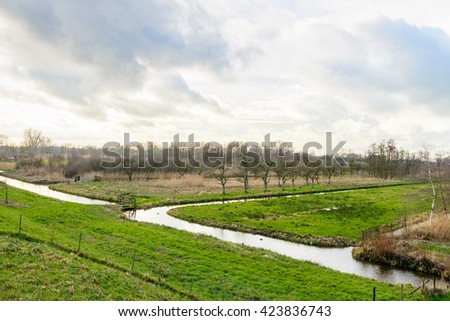 Polder landscape in the Netherlands as seen from the dike. Traditionally there are several water courses to control the water level. - stock photo