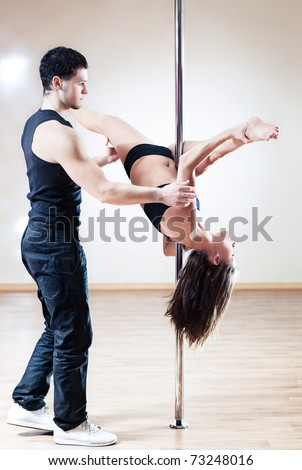 Pole dance trainer. Young man training woman. - stock photo