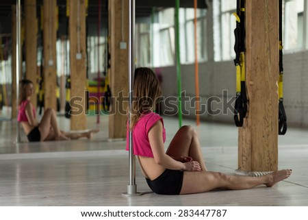 Pole dancer sitting on the floor and resting after training - stock photo