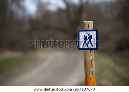 Pole with sign showing a walking path in scandinavian forest - stock photo