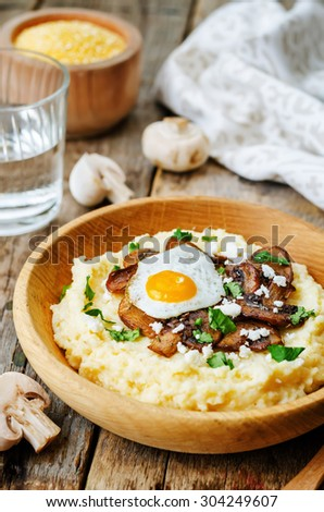 polenta with caramelised mushrooms, egg, cilantro and cheese. the toning. selective focus - stock photo