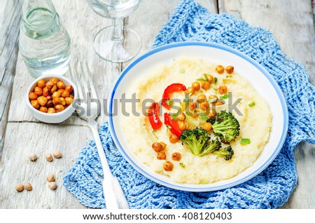 Polenta with roasted vegetables and chickpeas on a white wood background. toning. selective focus - stock photo
