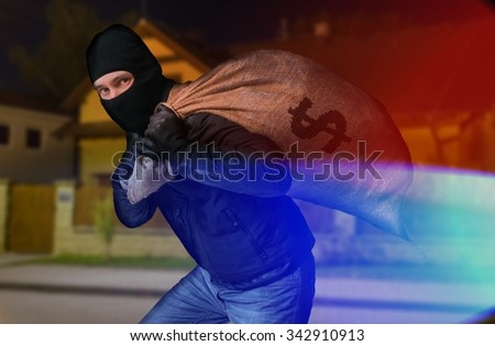 Police arrested thief with full bag of money at night. - stock photo