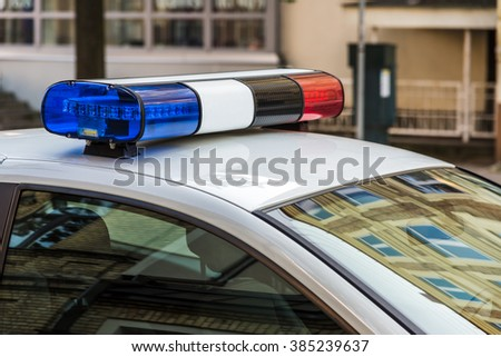 Police car in the street with a siren light - stock photo
