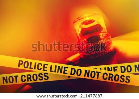 Police Line Do Not Cross Yellow Headband Tape and Orange flashing and revolving light. Murder Scene Police Ribbon. - stock photo