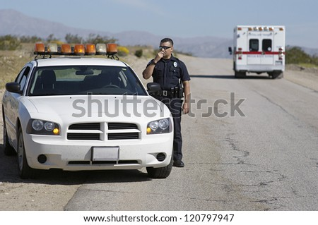 Police officer communicating on radio standing by car - stock photo