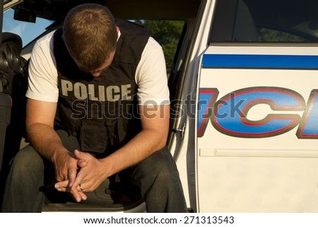 Police officer contemplates a rough day - stock photo