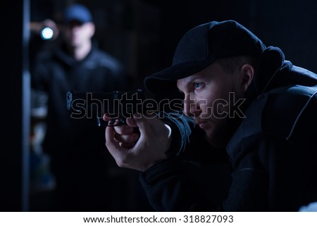 Police officer holding handgun during police intervention - stock photo