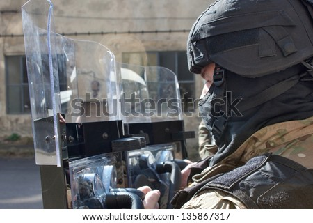 police officer in a protective helmet and visor, preparation for the demonstration - stock photo