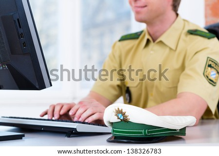 Police officer in police station working on the computer, on a case or registering a complaint - stock photo