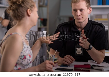 Police officer interrogating woman at police station - stock photo