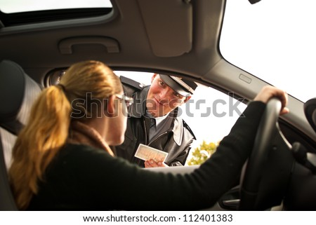 Police officer is doing a traffic check and is looking at a drivers license - stock photo