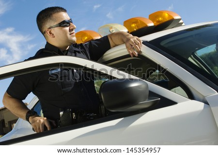 Police Officer Leaning on Patrol Car - stock photo