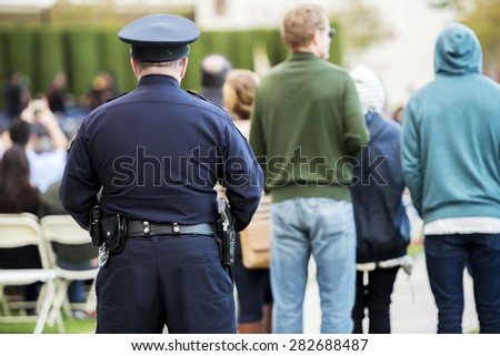 Police officer observes crowed  - stock photo