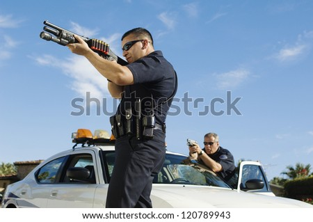 Police officers aiming with gun by car - stock photo