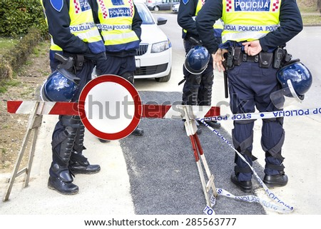 Police officers in hi-visibility jackets and protective shields on duty - stock photo