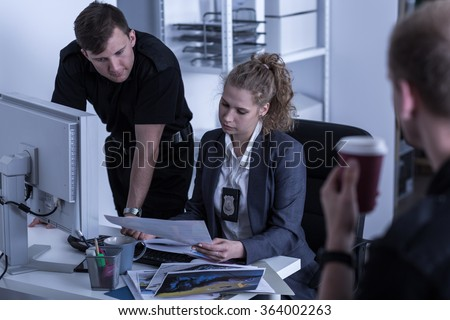 Police officers working at criminal investigation department - stock photo