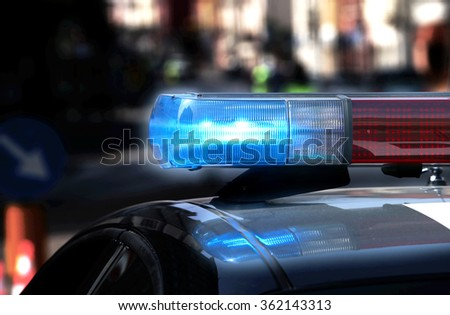 Police patrol car with flashing lights and siren on during the night raid against crime - stock photo