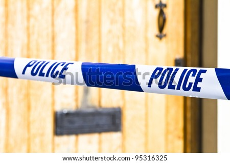 Police tape strung across a front door with shallow depth of field - stock photo