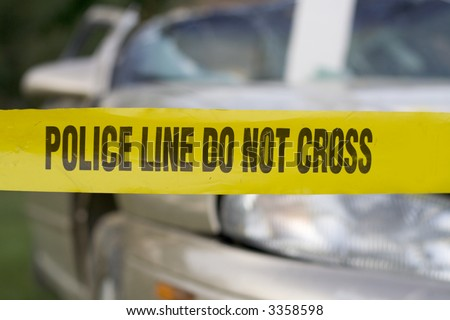 Police warning at an accident scene with a badly damaged car - stock photo