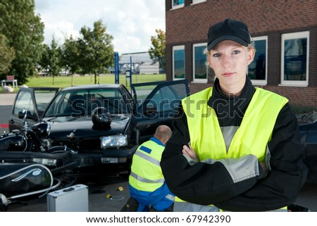 Police woman posing on the site of a car crash, with a paramedic working in the background - stock photo