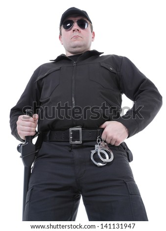 Policeman wearing black uniform and glasses standing confidently - stock photo
