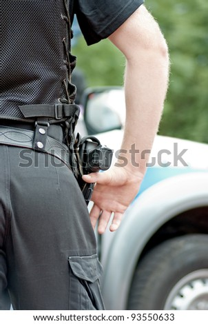 Policeman with the gun, police car in the background - stock photo