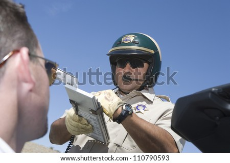 Policeman writing fine bill for a driver - stock photo