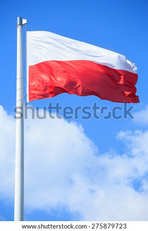 Polish flag on a background of blue sky - stock photo