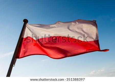 Polish flag on the mast against blue sky - stock photo