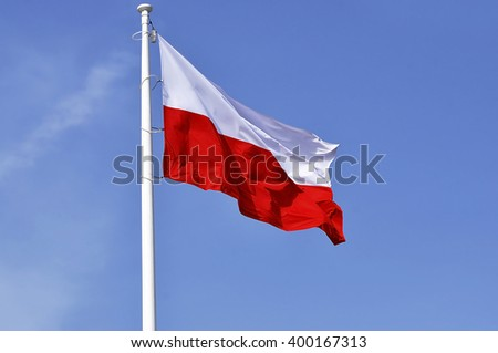 Polish national flag and blue spring sky - stock photo