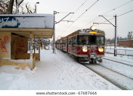 Polish train station at winter with train in motion - stock photo