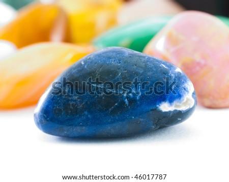 Polished dark blue lazurite gemstone in front of gemstone collection - stock photo