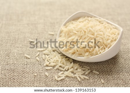 Polished long rice grains in white ceramic bowl on sackcloth background - stock photo