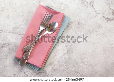 Polished metal tableware casually arranged on cloth mint and coral napkins lay on a white marbled counter or table with a top down perspective and copyspace. - stock photo