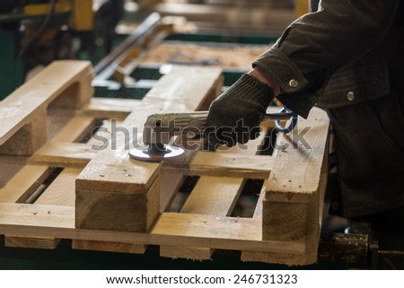 Polishing of wooden pallet on a production line - stock photo