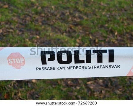 Politi, danish police barrier sign with meadow in background - stock photo