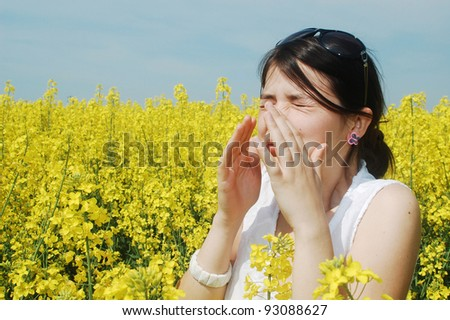 Pollen allergy, girl sneezing in a field of flowers - stock photo