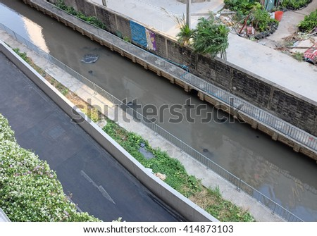 Polluted canal and dirty sewer in an urban area in Bangkok thailand. Polluted water and garbage are serious subject of Thailand - stock photo