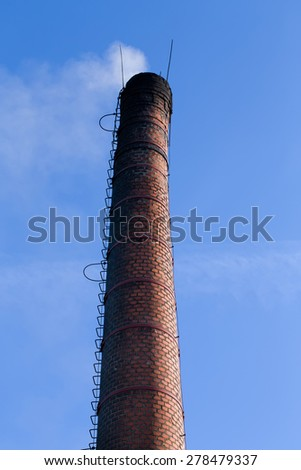 Polluting white smoke coming out of chimney against blue sky - stock photo