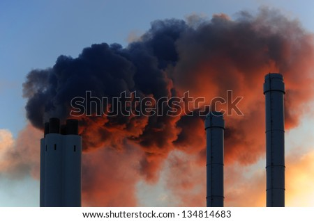 Pollution concept of smoking chimneys. The setting sun illuminates the vapor from below, giving it an ominous impression, like that of volcano smoke. - stock photo
