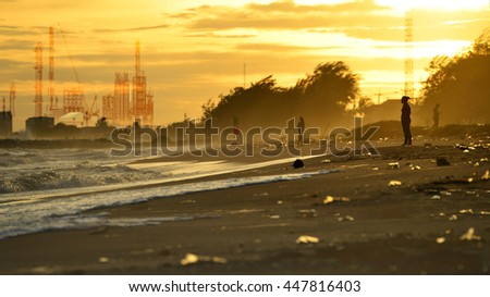pollution industry concept , Beach pollution. Plastic bottles and other trash on sea beach and Factory pipe polluting air against sunset, environmental problems, smoke from chimneys . - stock photo