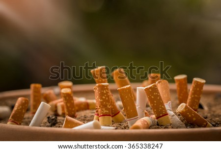 Pollution,Smoking,Danger,Bush, Brown's ashtray filled with garbage lining the gallery. Background on the warm morning air. - stock photo