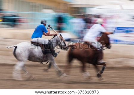 Polo players ride towards the goal, motion blur caused by fast panning. Unrecognizable person. - stock photo