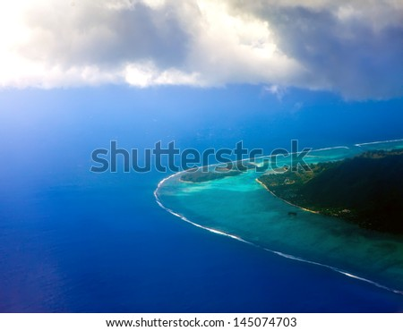 Polynesia. The atoll in ocean through clouds. Aerial view - stock photo