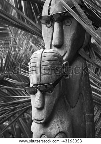Polynesian carved wooden idols in sunglasses - stock photo