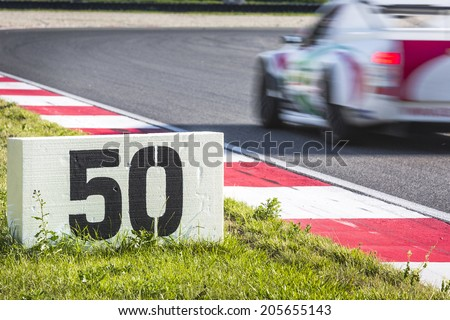 Polystyrene slab next to the curb stones on a race track indicates the breaking point for a passing race car, approaching the apex - stock photo