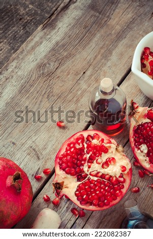 Pomegranate and bottles of essence or tincture on wooden rustic table, top view - stock photo