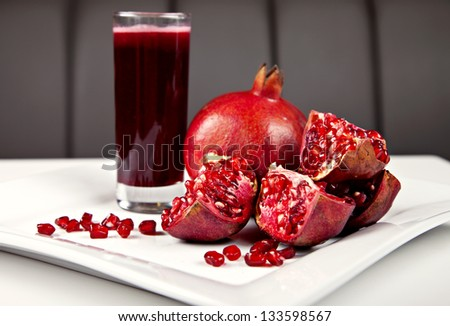 Pomegranate and juice on white plate - stock photo